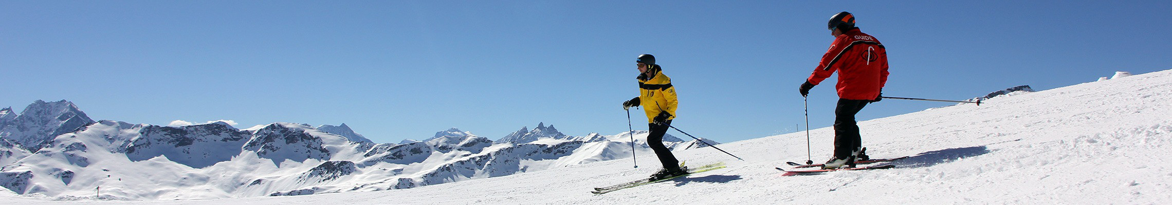 Photo: Un tandem de skieurs alpins sur fond de sommets enneigés.